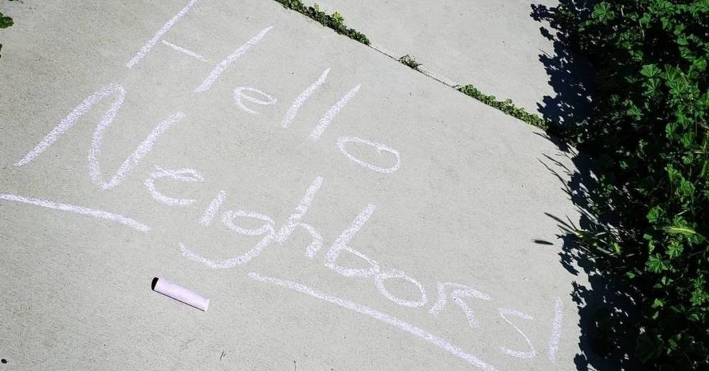 Hello neighbors written in white chalk on a sidewalk as a way to be social - something forgotten in social media